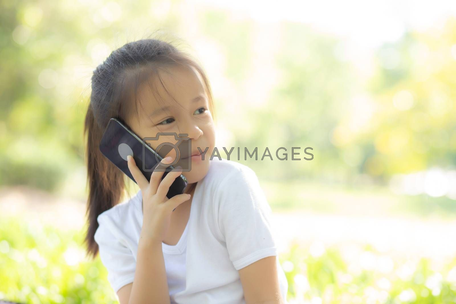 Beautiful portrait asian child happy and talking smart mobile phone in the nature park in summer, asia kid cellphone, little girl casual relax and leisure, communication concept.
