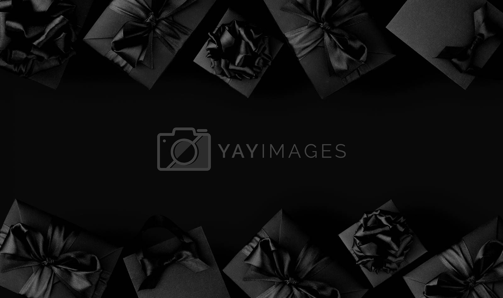 Black shopping bags and gift boxes on black background with copy space for text, Black Friday sale shopping concept