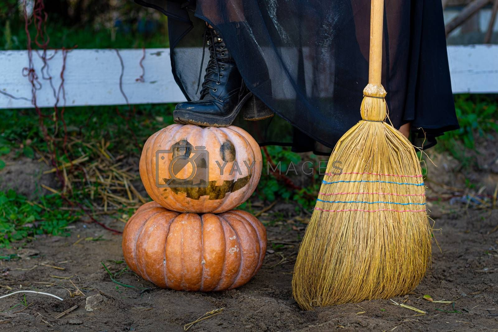 On a pumpkin with a drawn scary face is a witch's foot, next to a broom, close-up