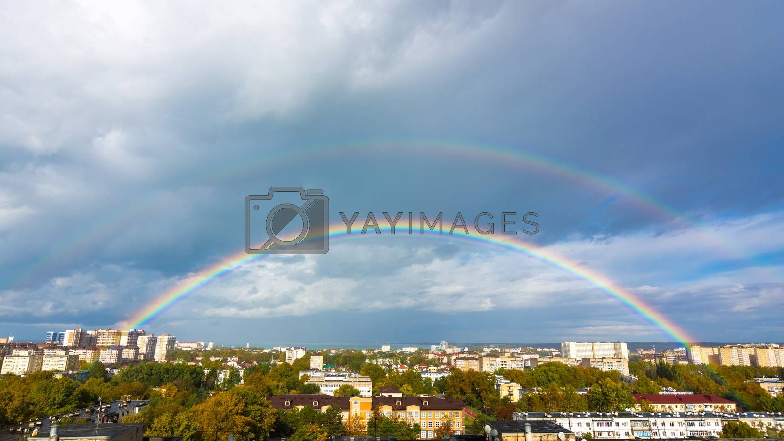 Double rainbow in the sky over the roofs of the resort city of Anapa, Russia