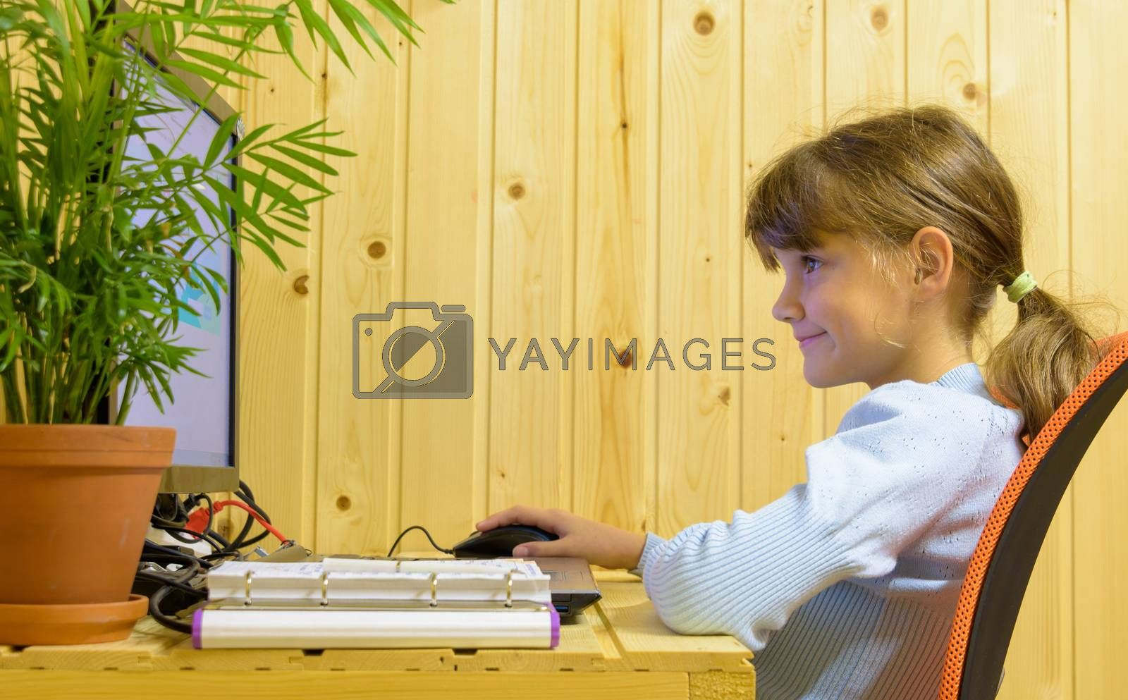 Happy girl takes online lessons at a computer in a country house