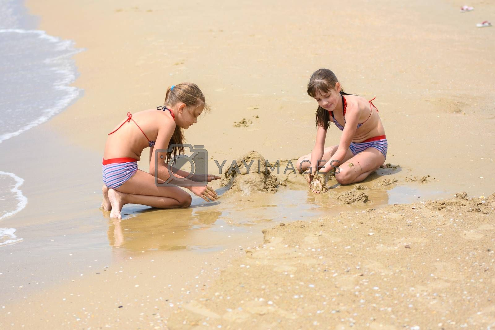 Two girls build sand castles on the seashore