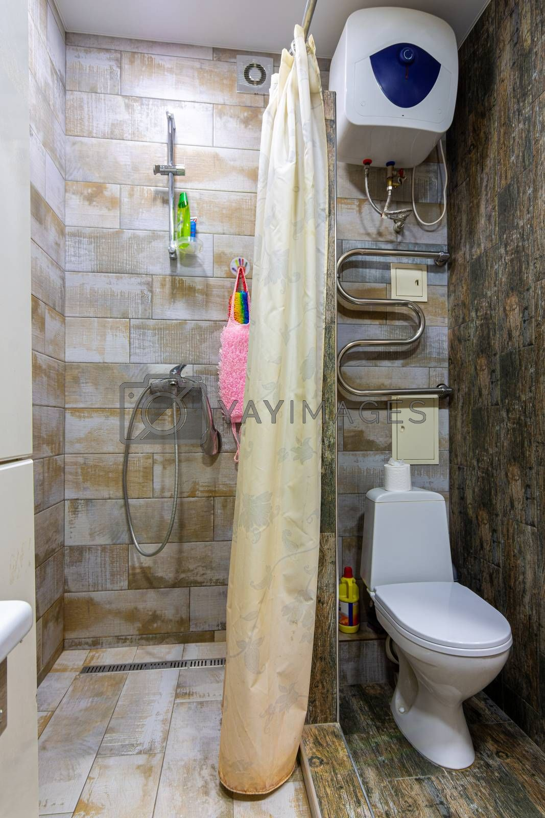 Small compact bathroom divided with shower curtain and toilet