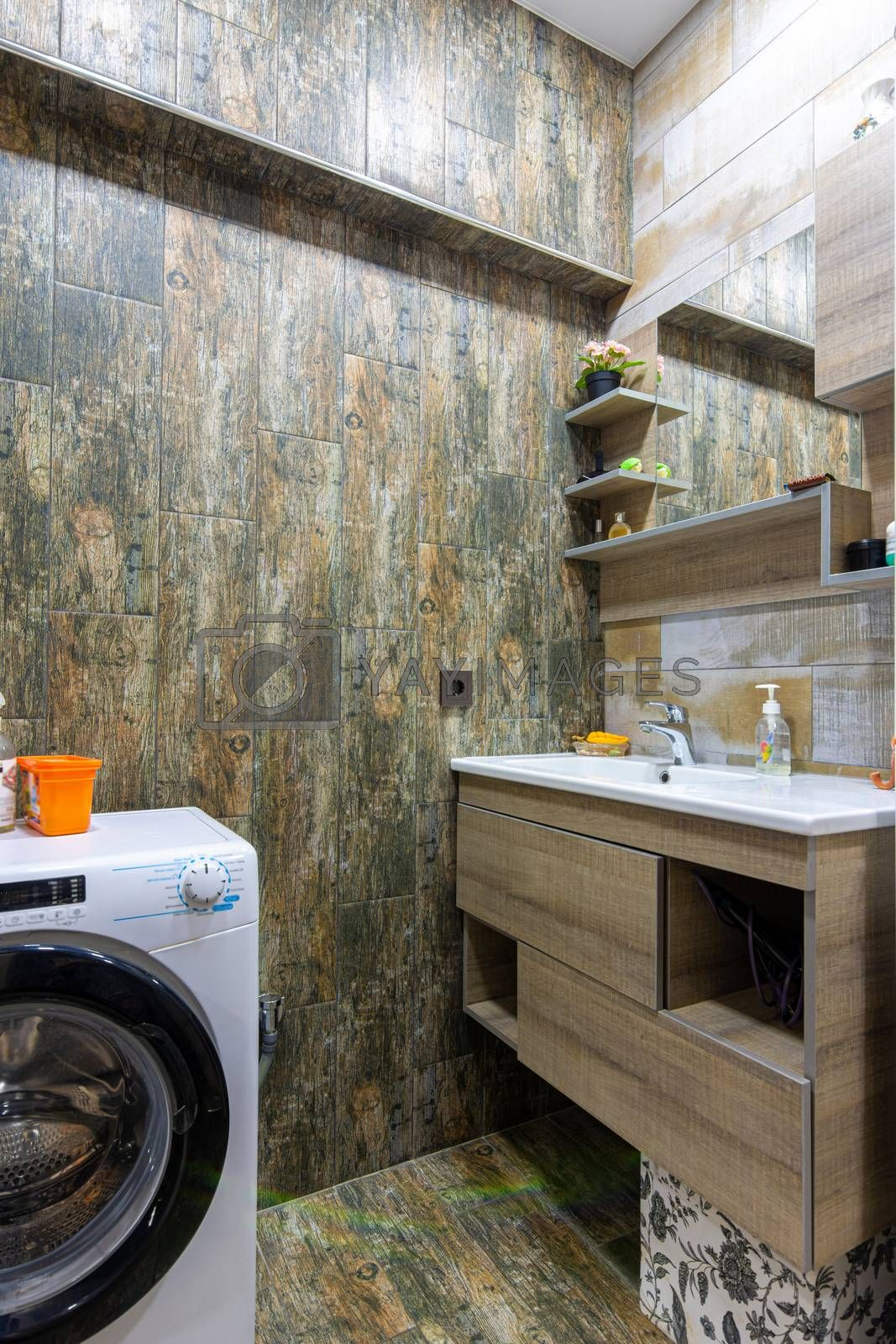 Bathroom interior with beautiful tiles, a view of the washbasin built into the furniture with a mirror and a washing machine