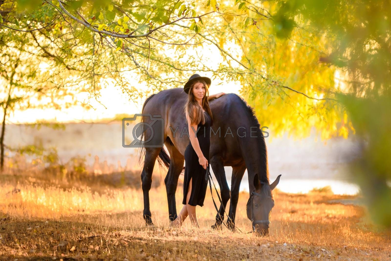 Girl walks in the forest with a horse at sunset