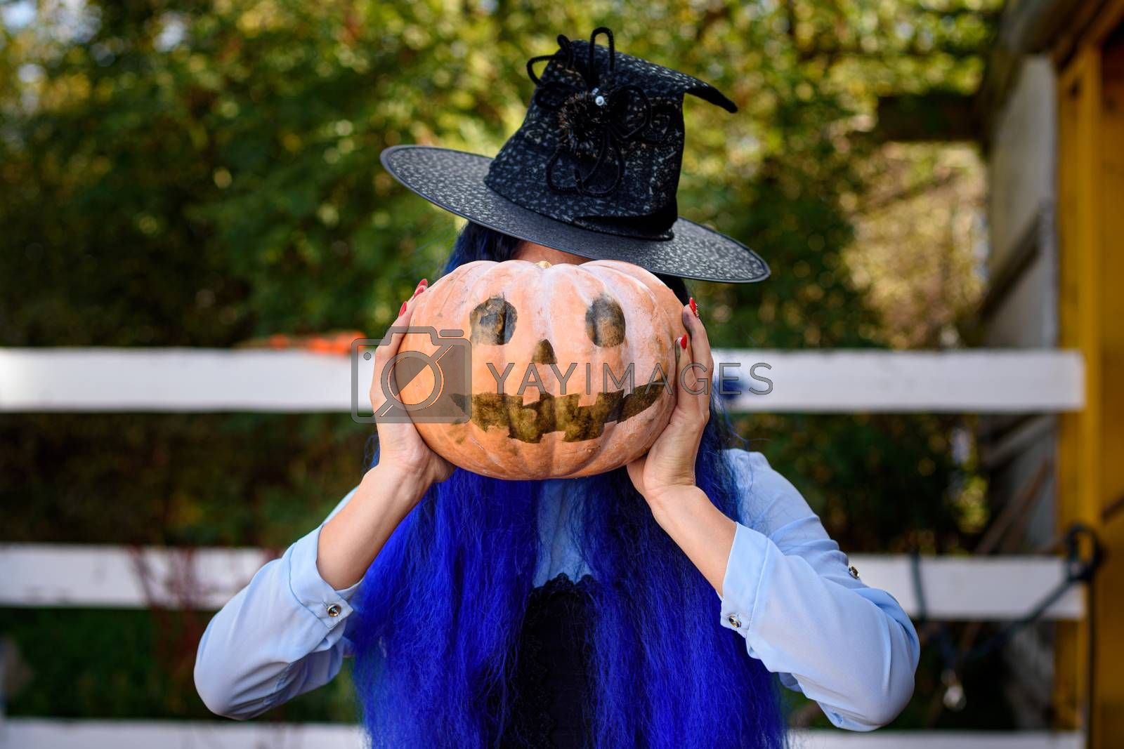 A girl dressed as a witch covered her face with a pumpkin with an evil face drawn in the style of a Halloween celebration