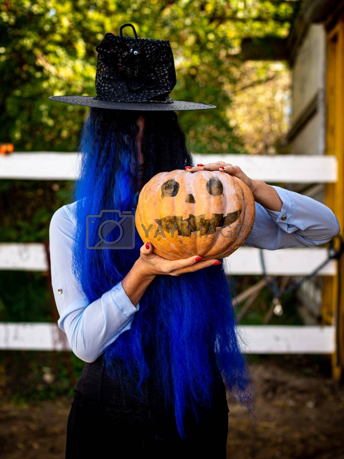 A girl with her hair covered face in a witch costume is holding a pumpkin with a painted face and a witch's cap