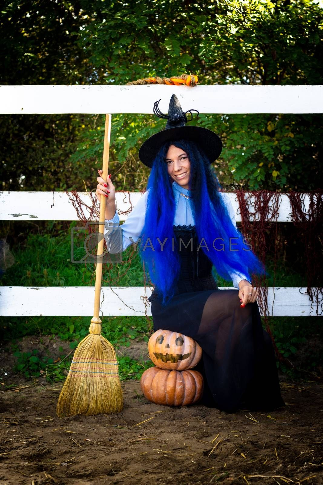 A girl in a witch costume sits on two pumpkins and holds a broom in her hands