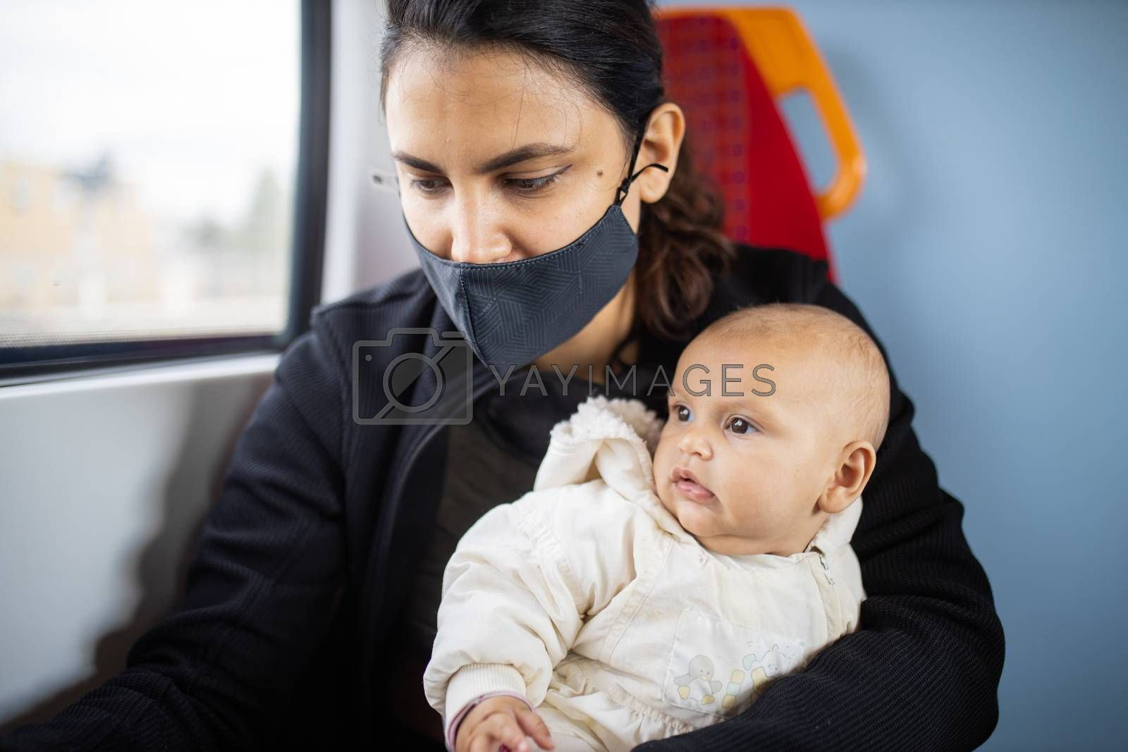 Woman wearing a face mask sitting next to a window in a bus and holding her distracted-looking baby