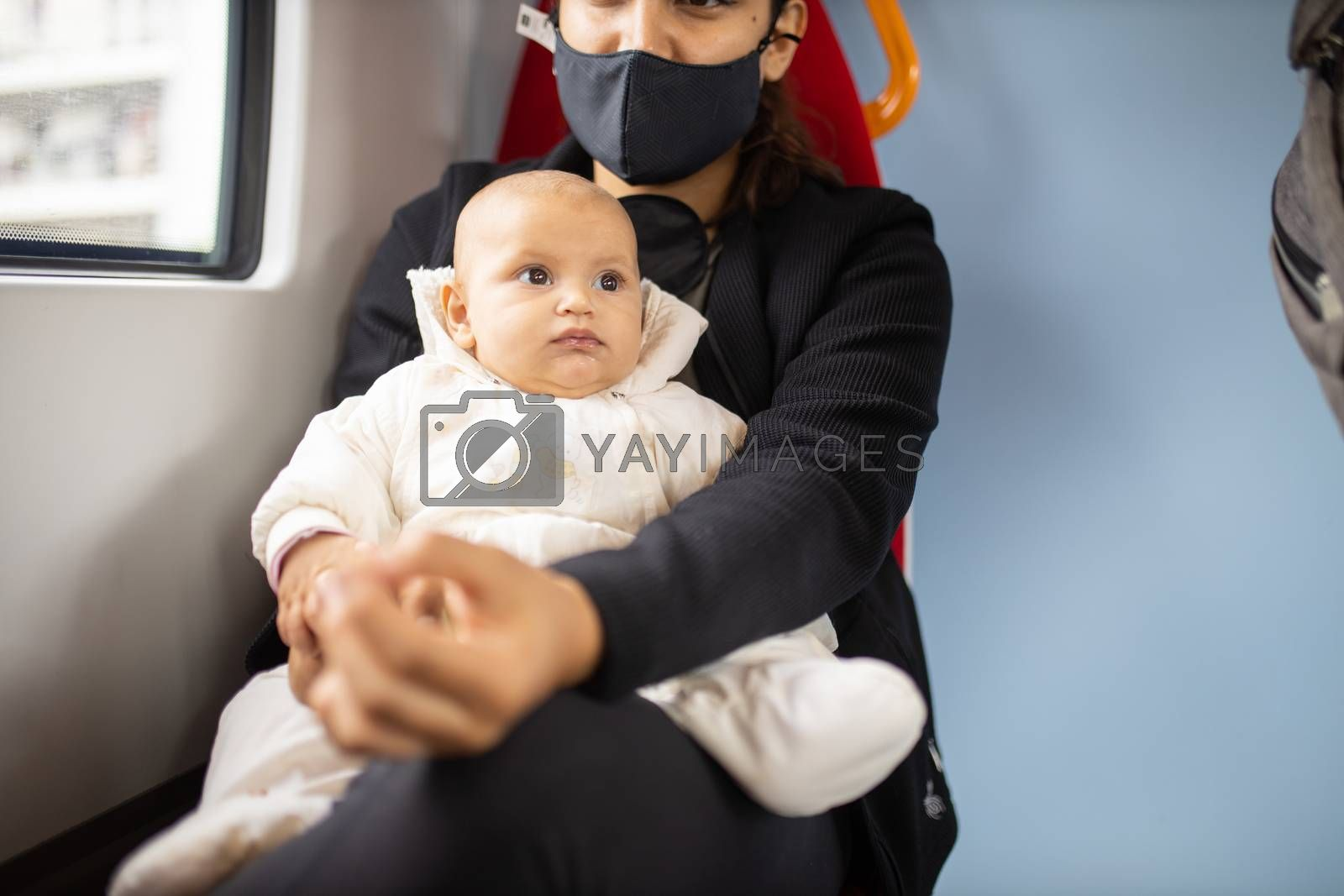 Baby in white clothing looking into the distance and resting on the legs of her mother who wears a face mask