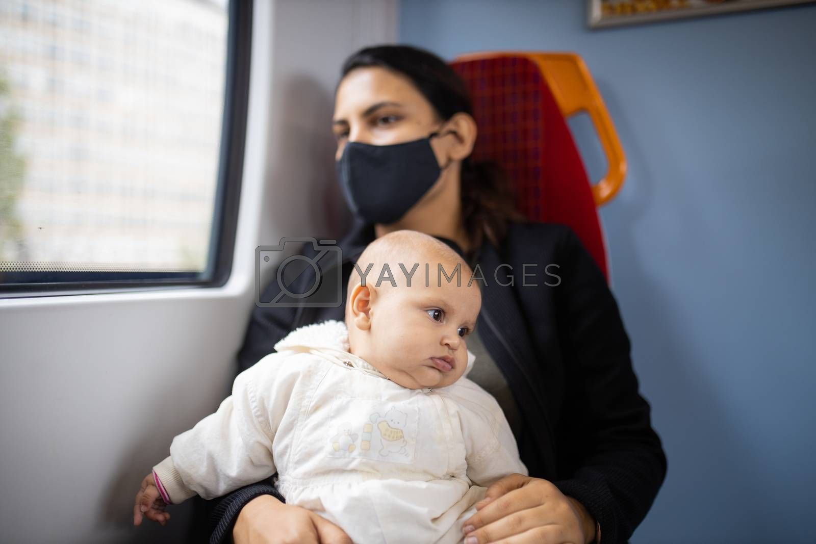 Woman wearing a black face mask sitting next to a window on a train and holding her baby who looks absently