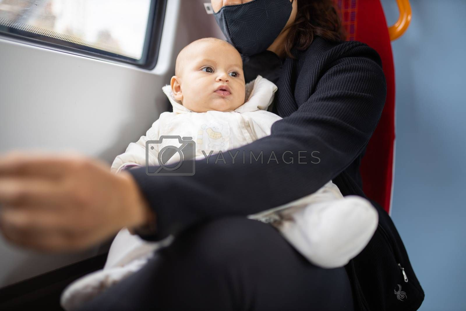 Distracted-looking baby in white clothing resting on the legs of her mother who wears a face mask and sits next to a window
