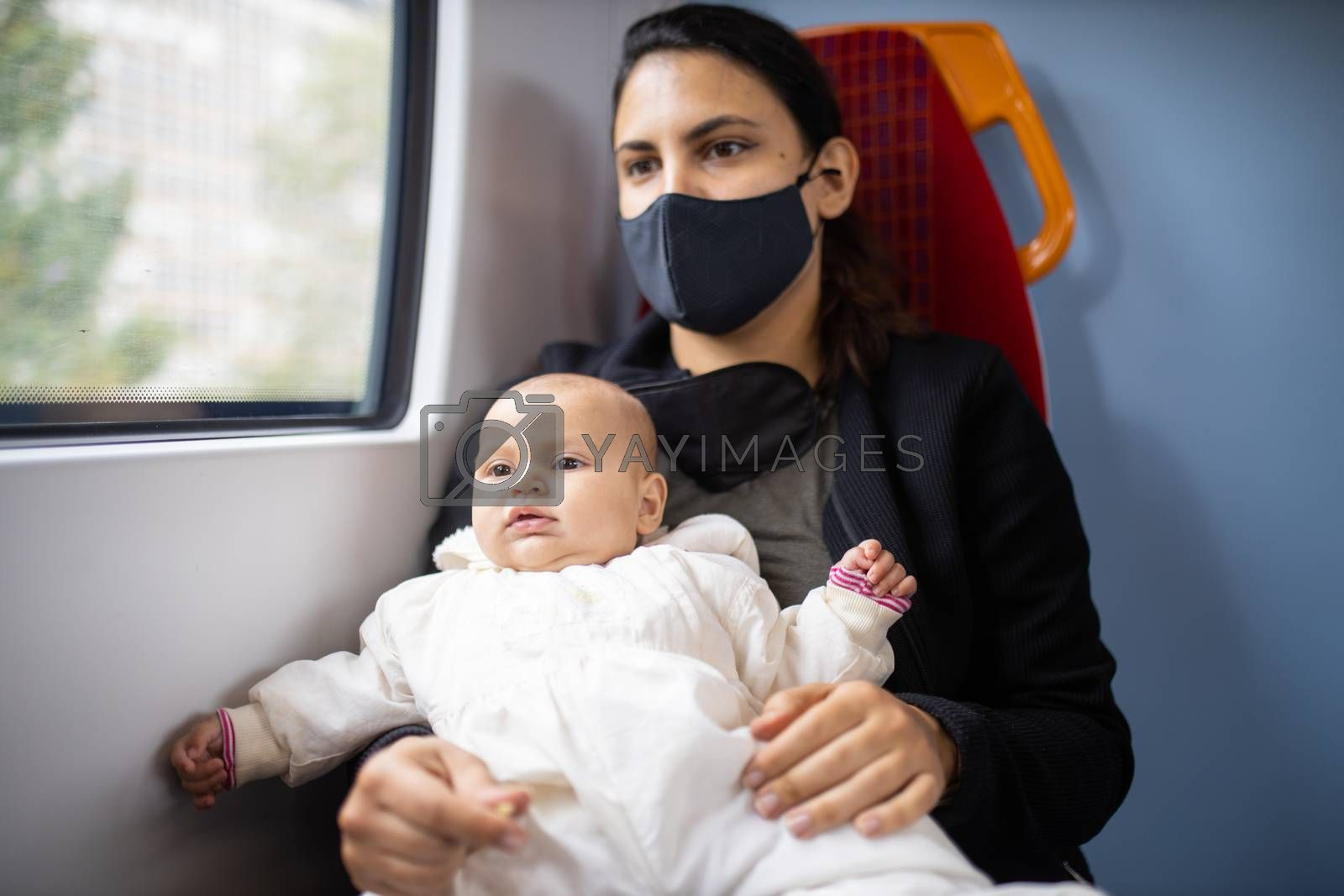 Woman wearing a black face mask sitting next to a window in a bus and holding her distracted-looking baby daughter