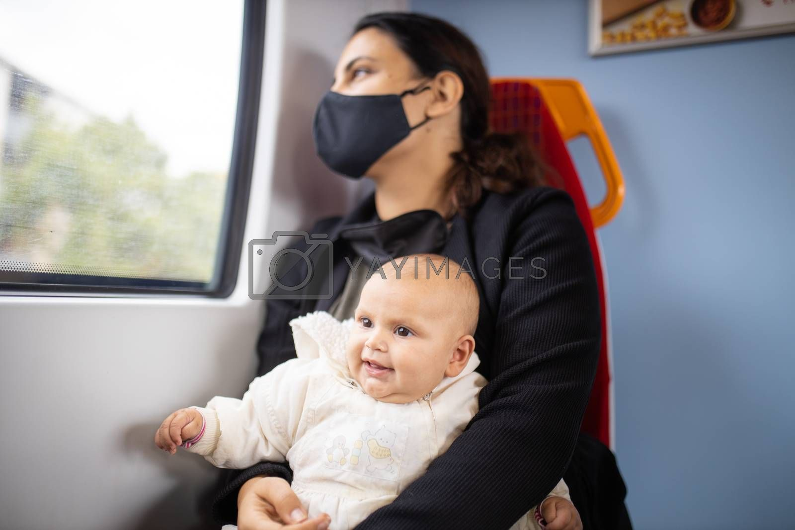 Woman wearing a face mask and black clothes and looking through the window of a train as she holds her smiling baby