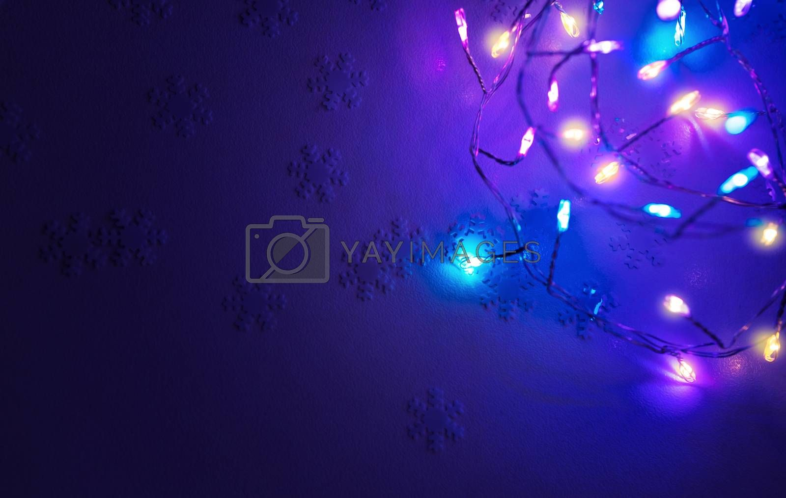 Christmas Background. Snowflake Confetti and Glowing Festoon on Blue Backdrop, Festive Greeting Card, Beautiful Decoration for New Year Celebration.