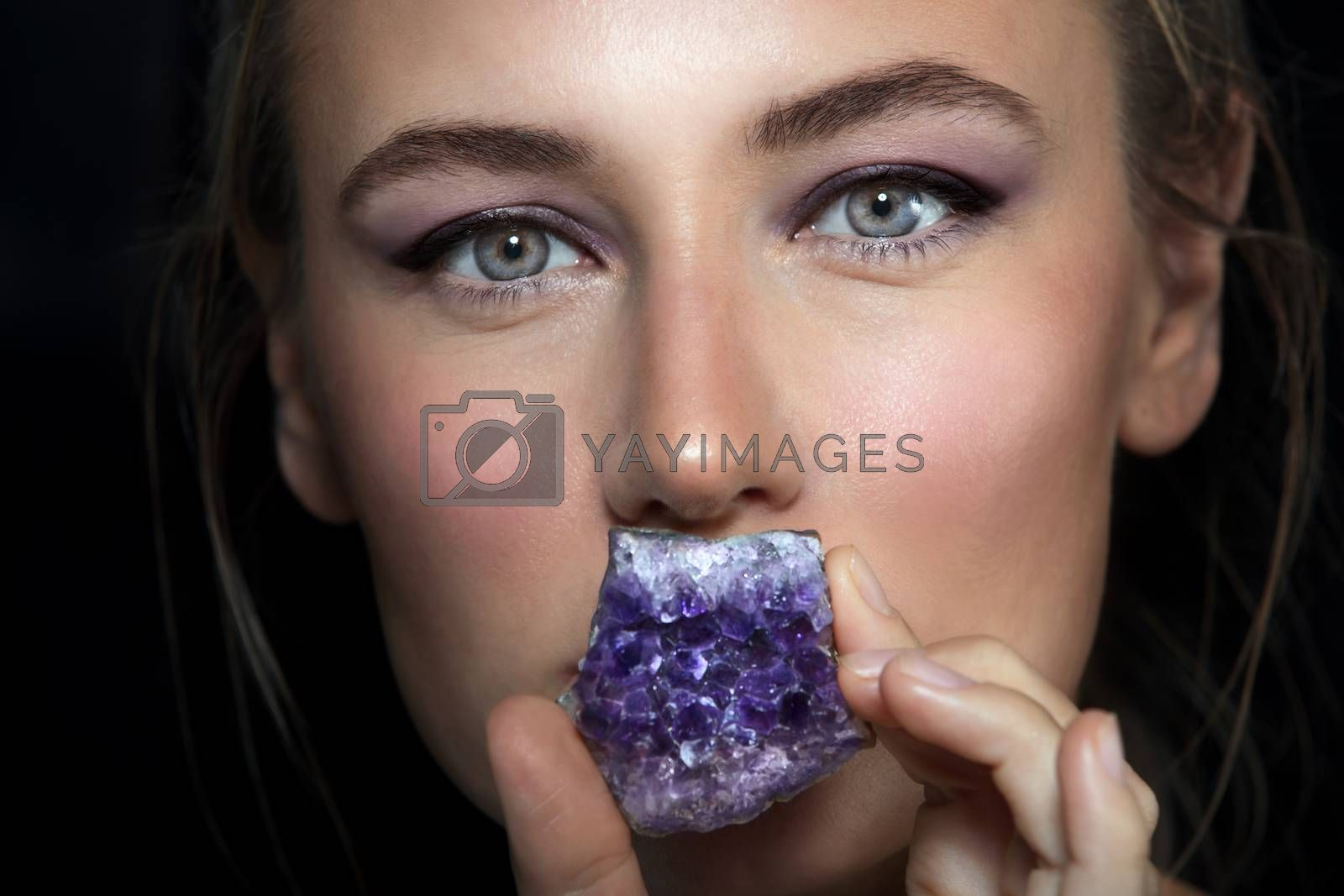 Closeup Portrait of a Gorgeous Woman Covered her Lips with Beautiful Purple Amethyst Stone. Fashion Silence.