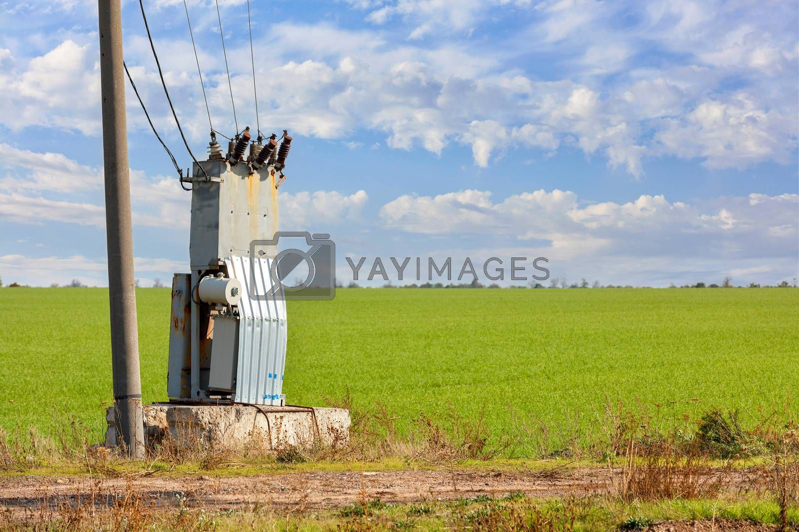 An old transformer station stands in the middle of a green field, near a concrete pillar, against a blue cloudy sky.