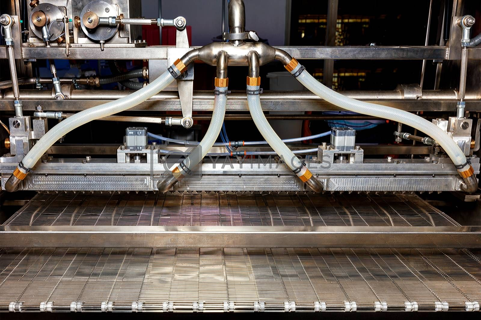 Spraying mechanism made of stainless steel on the conveyor of a production line in the food industry.