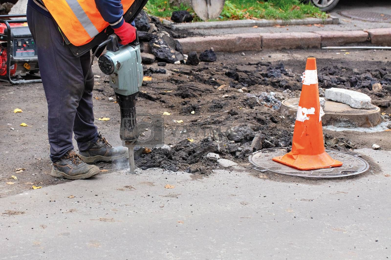 A road worker, dressed in reflective clothing, uses an electric jackhammer to rip old asphalt off the road and uses a gasoline generator, copy space.