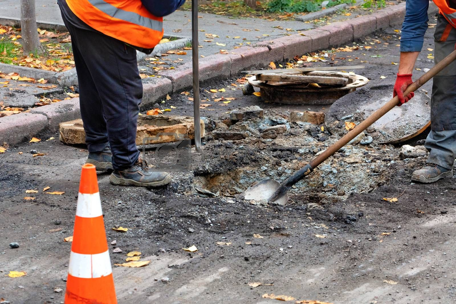 Road workers, dressed in reflective clothing, use a crowbar and a shovel to dismantle an old sewer manhole, copy space.