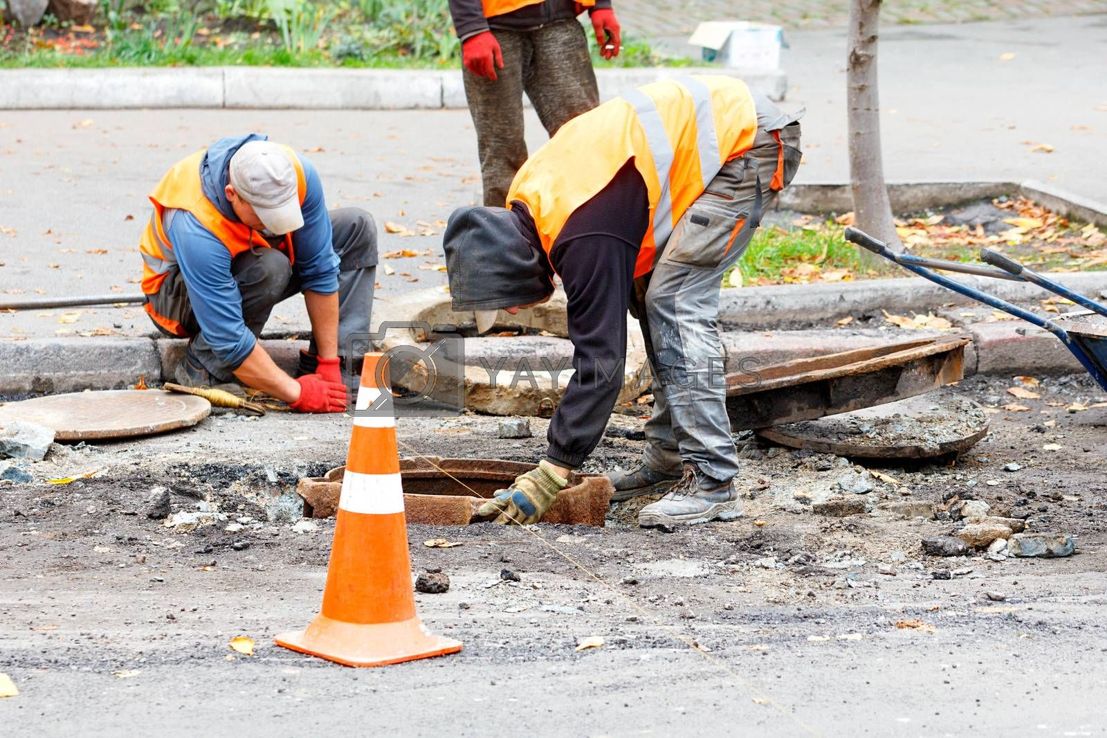Road workers on a fenced-in stretch of road, dressed in reflective clothing, replace an old sewerage manhole.