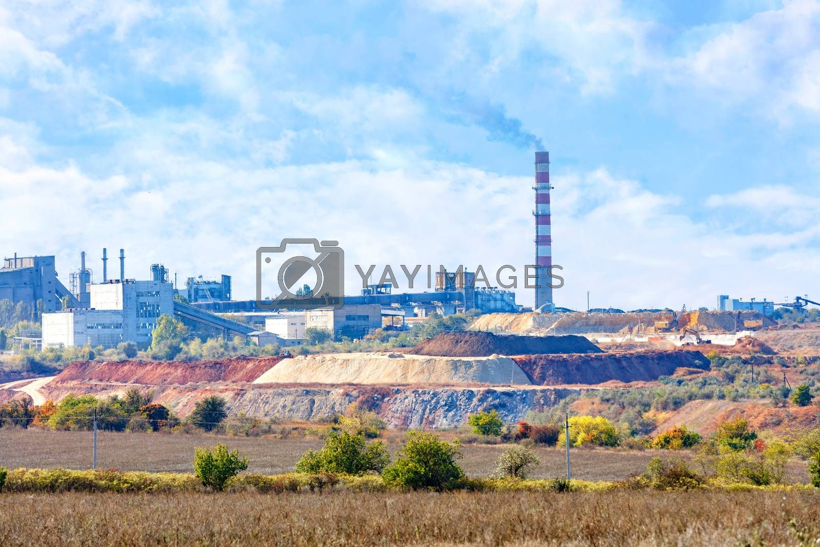 Sand and clay quarry, cement production complex on the horizon with a tall chimney against a blue cloudy sky, copy space.