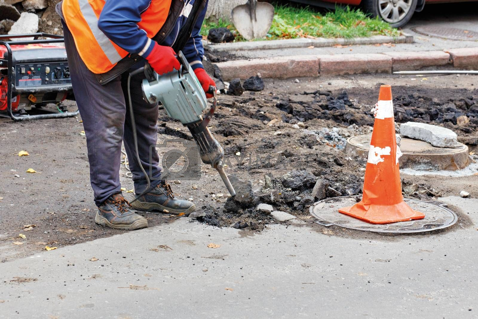 A road worker in reflective clothing breaks old asphalt off the road with an electric jackhammer.