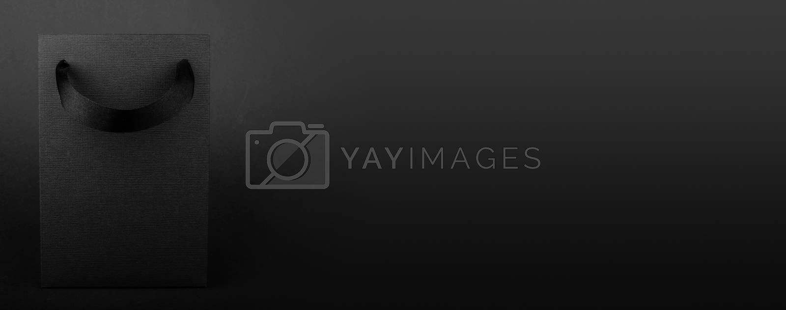 Black Friday blank empty paper bag with copy space for text and logo on dark background sale concept banner backgrounds