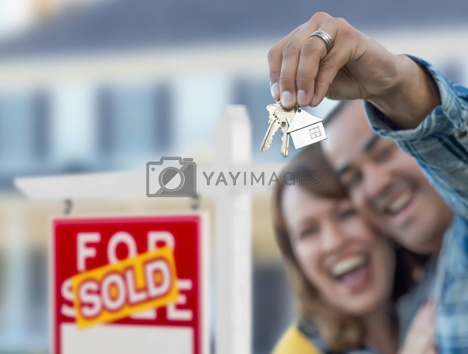 Mixed Race Couple in Front of Sold Real Estate Sign and House with Keys.