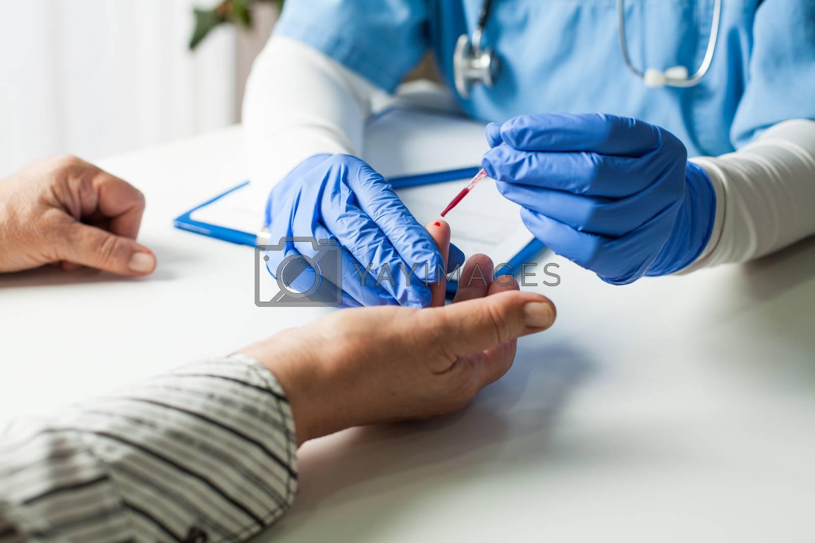 NHS UK doctor taking patient blood sample,serologic finger prick PRP blood antibodies test to determine whether person developed immunity to novel Coronavirus,global COVID-19 pandemic health crisis