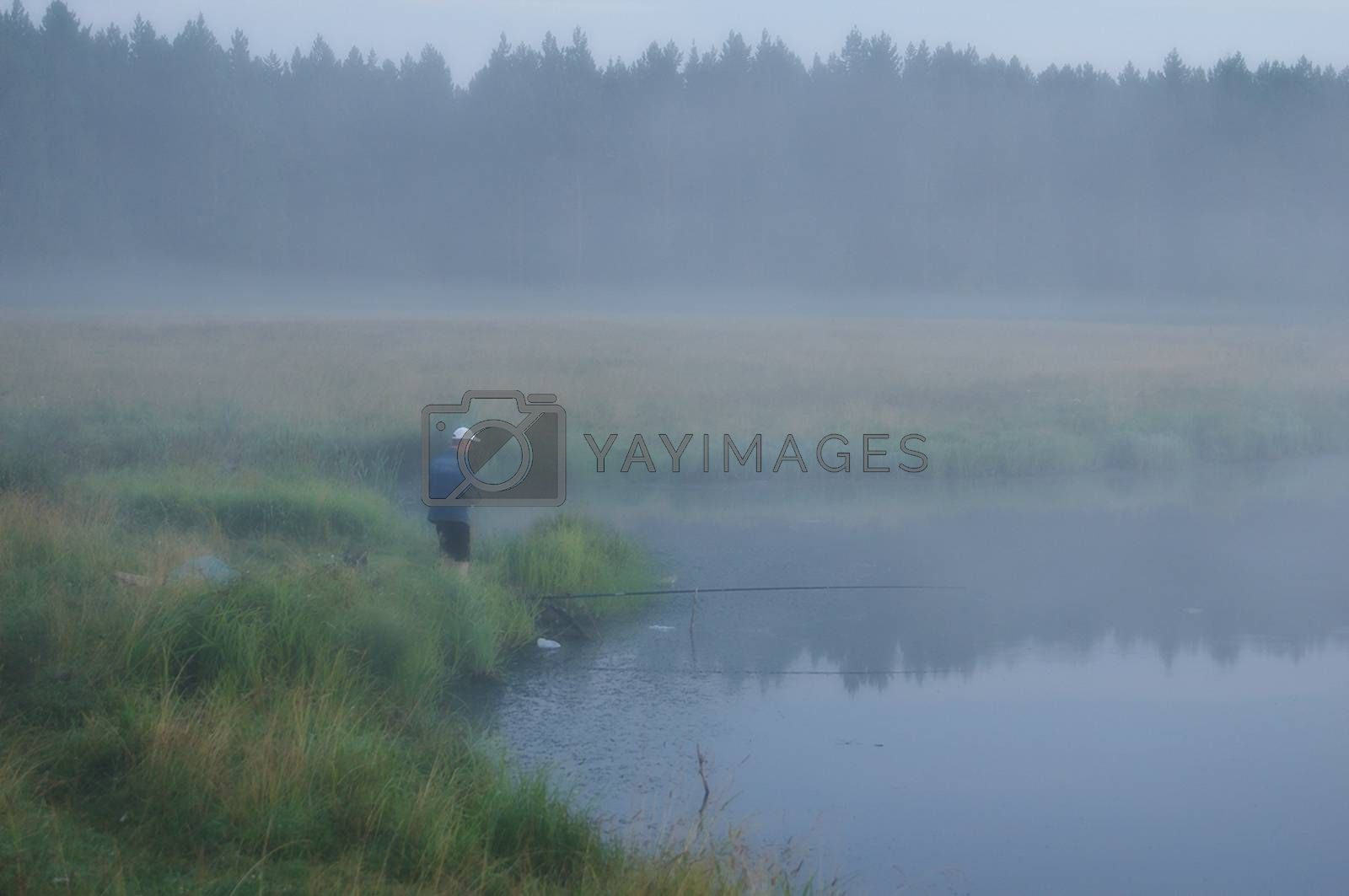 A fisherman in the fog catches fish on the pond.