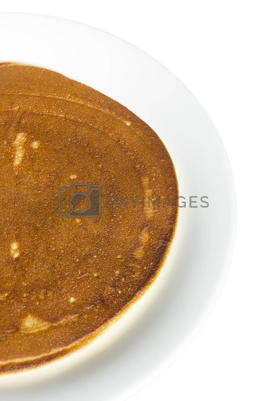 Freshly baked pancake on a plate on a white background