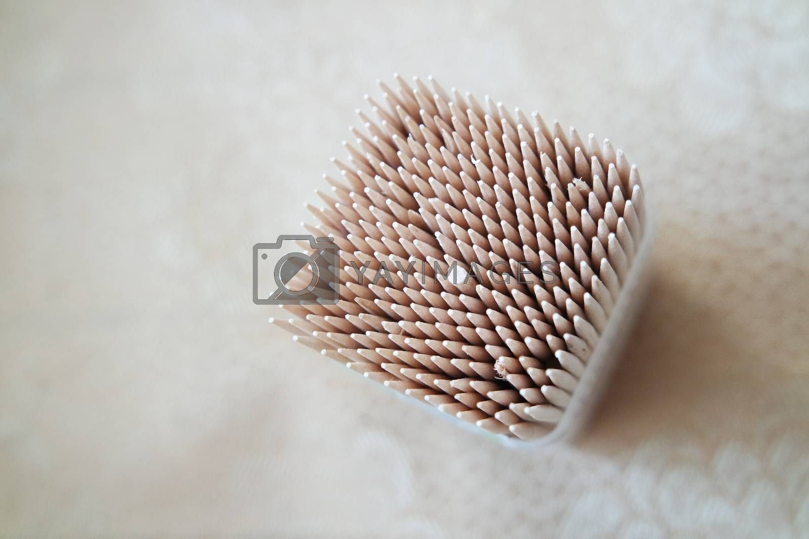 High angle top view of wood needles or wooden tooth picks arranged in a white plastic box container