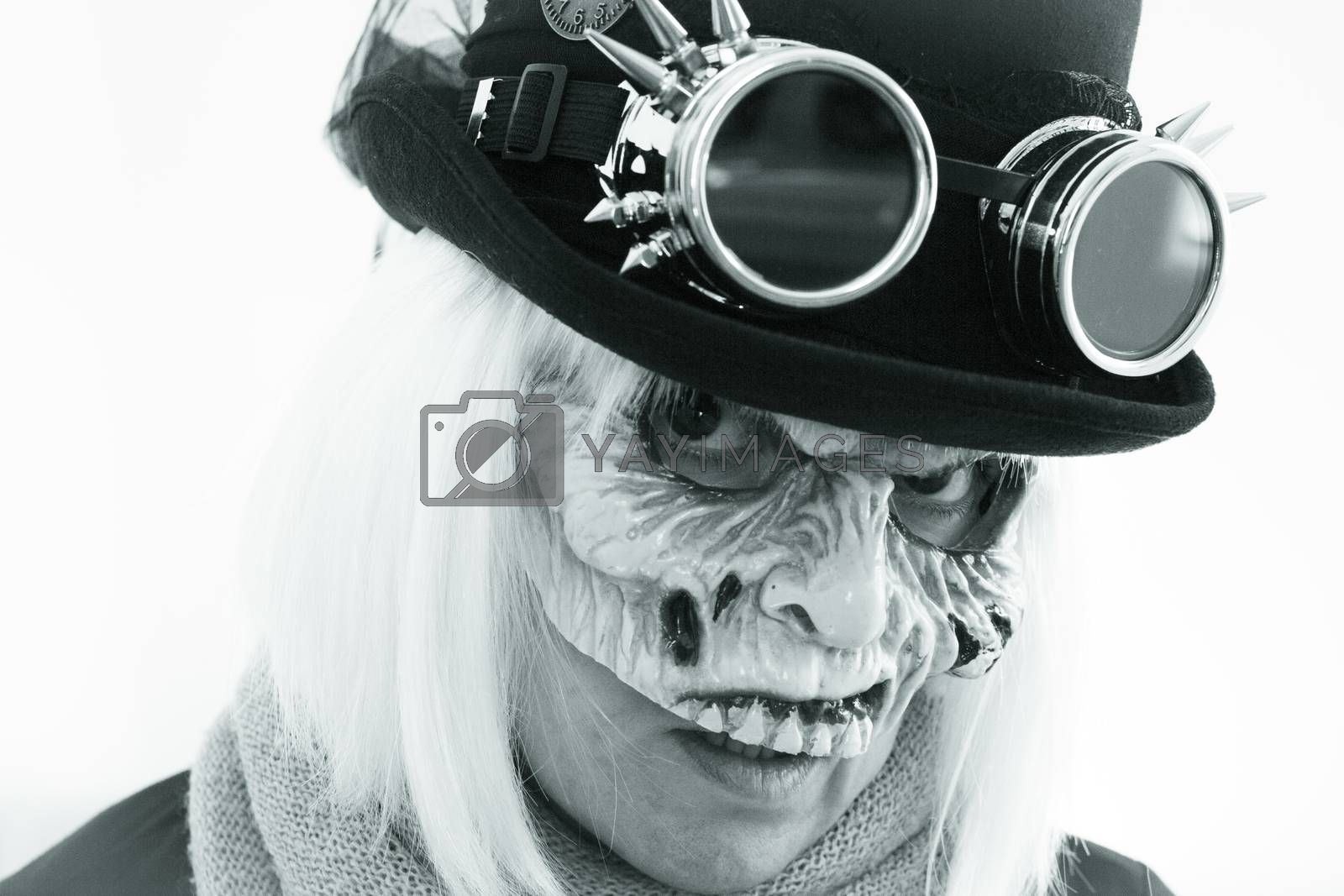 Woman with monster face and black hat wearing steampunk glasses. White hair.