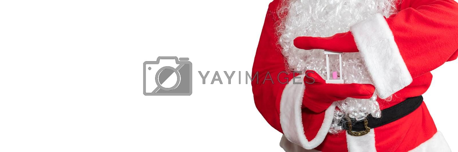 Santa Claus holding a white sand clock with both hands. Time is out. New year's eve concept. Isolated on white background. Banner size, copy space.