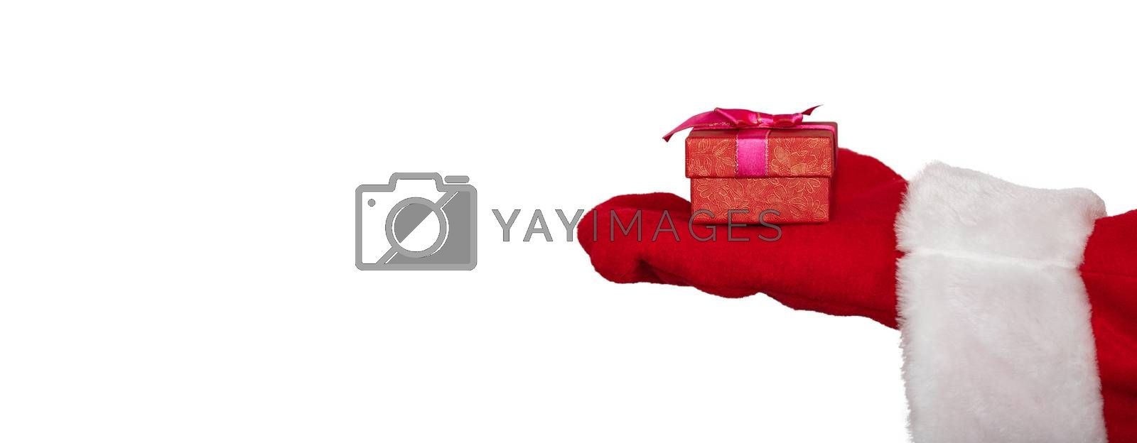 Santa Claus's hand holding a red box with a ribbon. Christmas gift concept. Isolated on white background. Banner size, copy space.