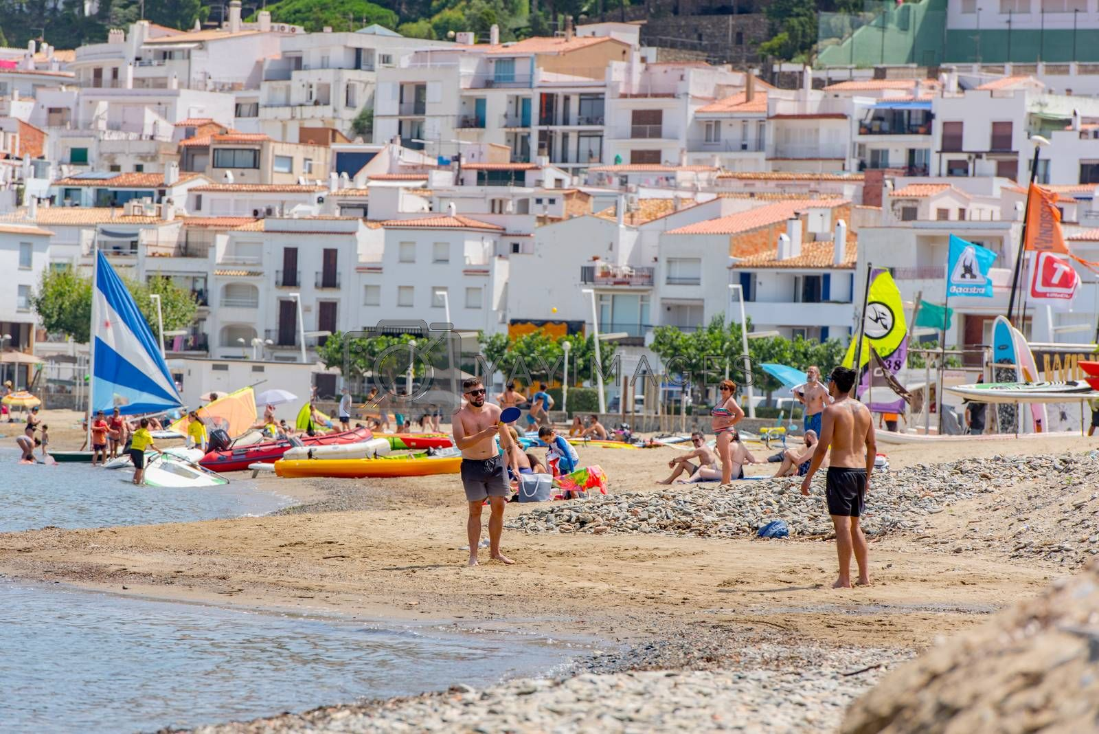 Port de la Selva, Spain : 9 July 2020 : People in the beach of Port de la Selva, one of the most touristic villages of Costa Brava, on August 9, 2013, in Port de la Selva, Catalonia, Spain.