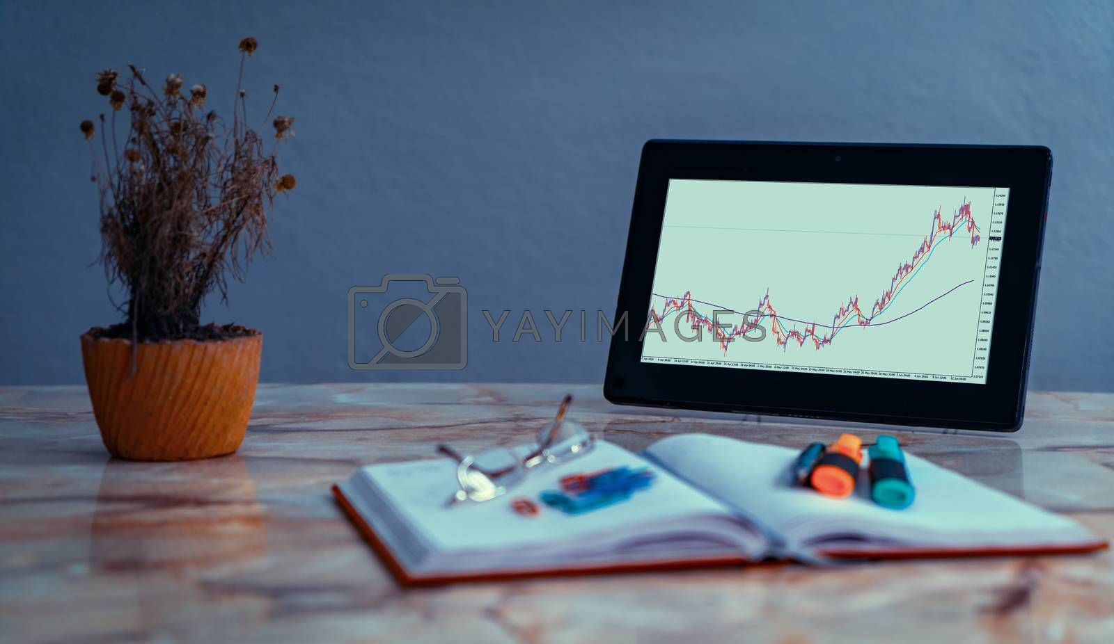 Screen of a tablet on a desk with a chart of currency pairs. On the desk there is an out of focus notebook