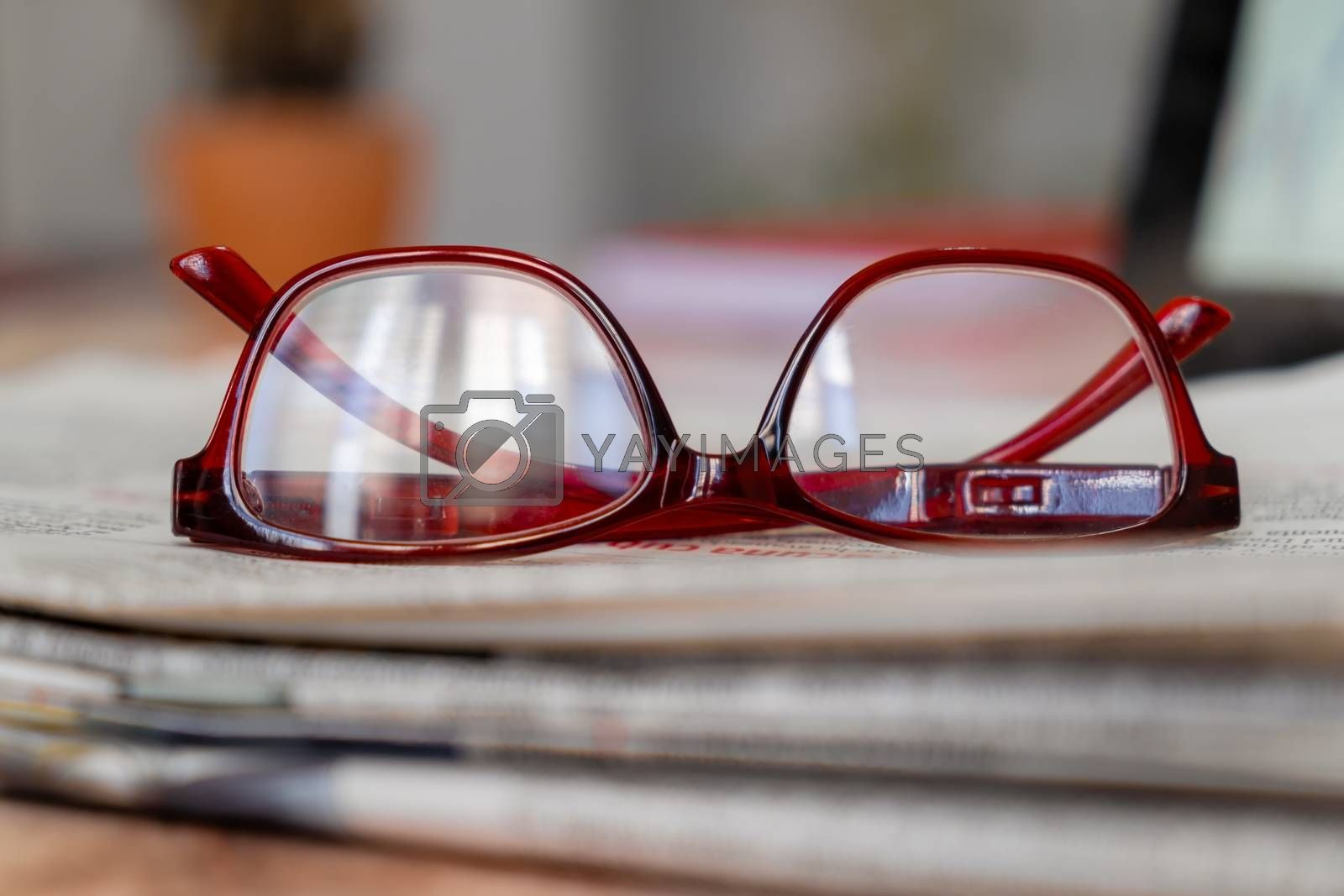 A pair of glasses on newspapers at a narrow foreground with a completely out of focus background.