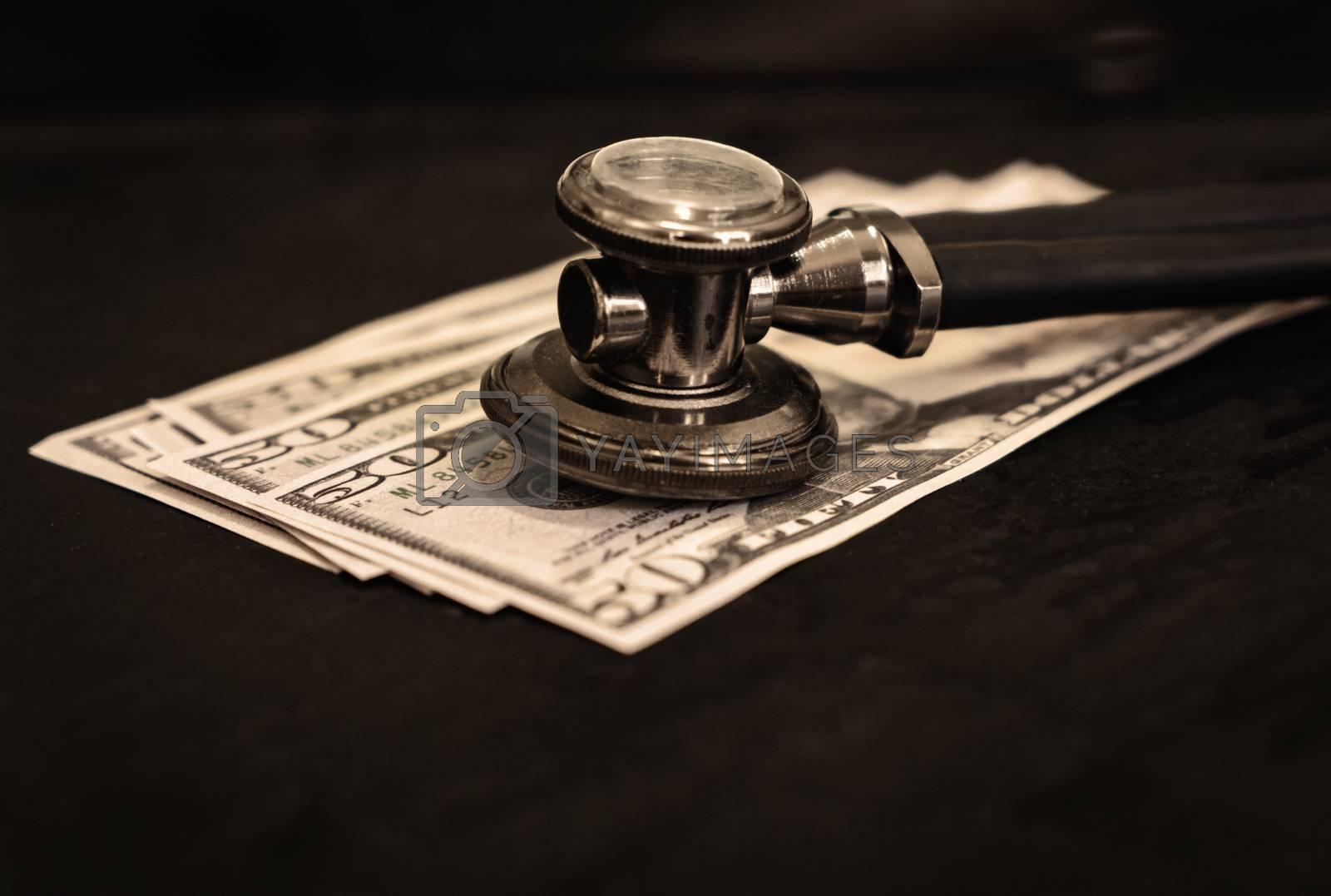 A stethoscope on three fifty dollar bills. Sepia toned photo
