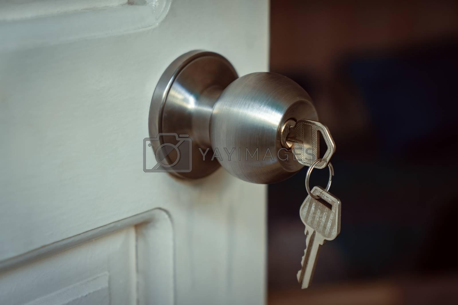 Key put in a knob lock on a white open door