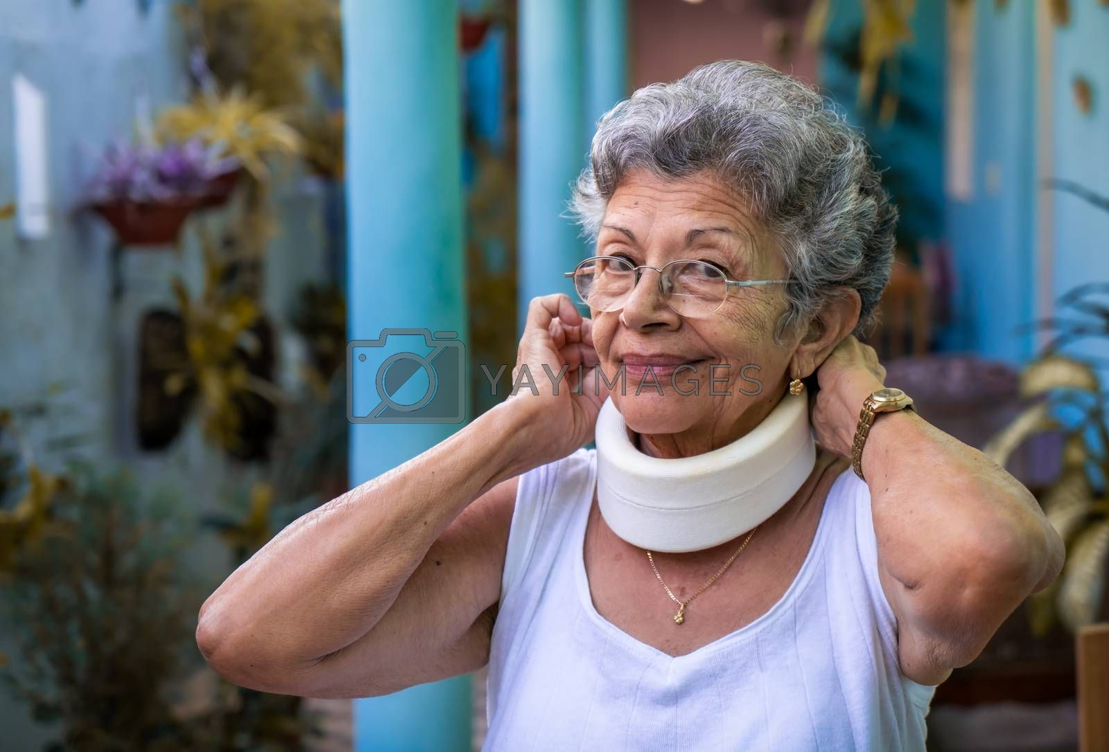 Smiling elderly woman putting on homemade looking cervical immobilizer collar