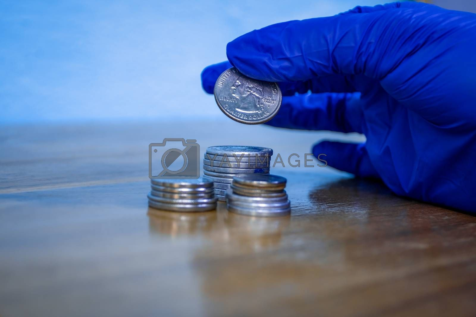 Protected hand with a blue glove holding a quarter of dollar over a group of coins