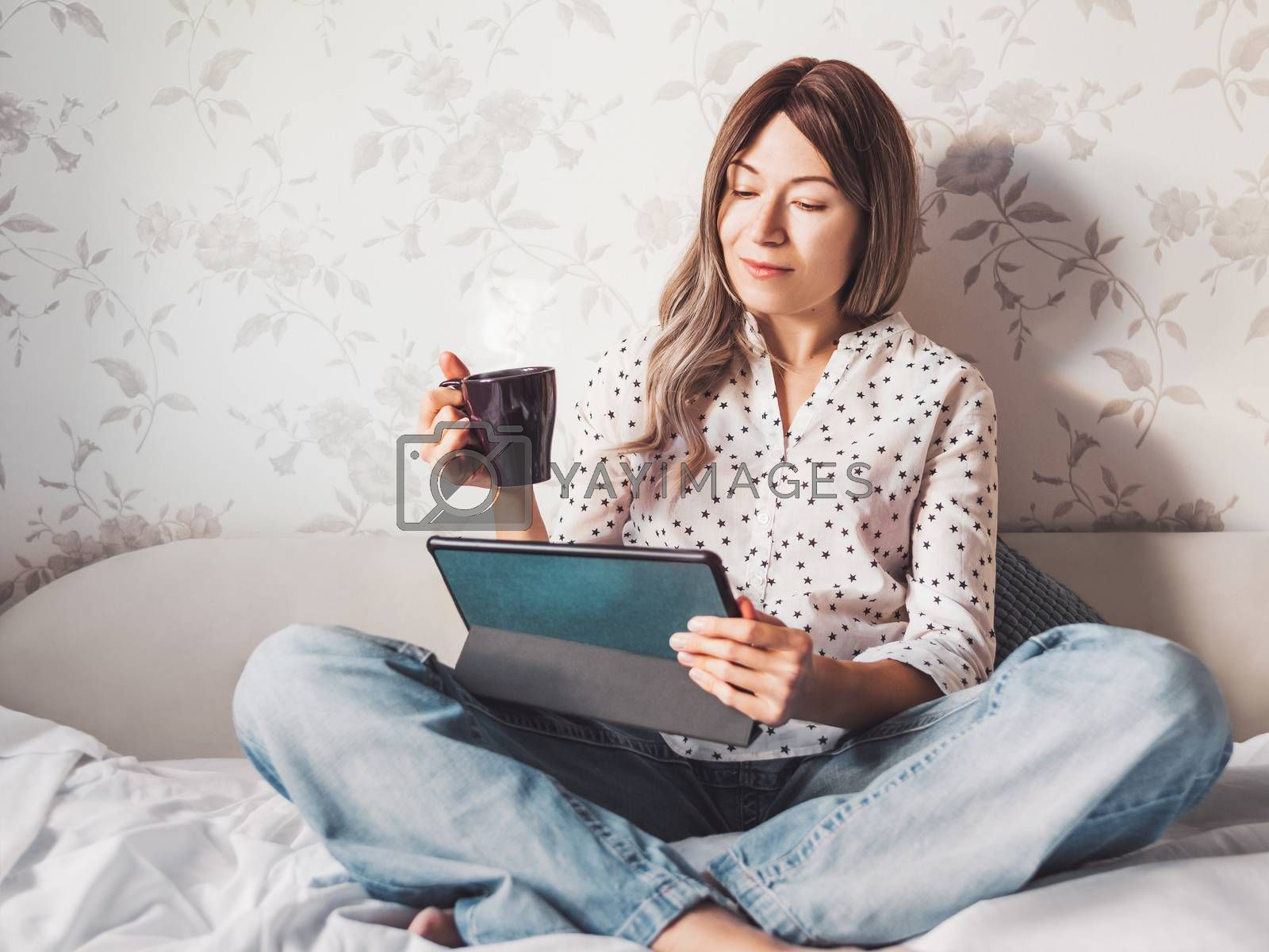 Woman sits on bed with tablet PC and cup of hot coffee. She watches online TV series. Online video call or conference, distance learning, remote education. Self isolation during quarantine.