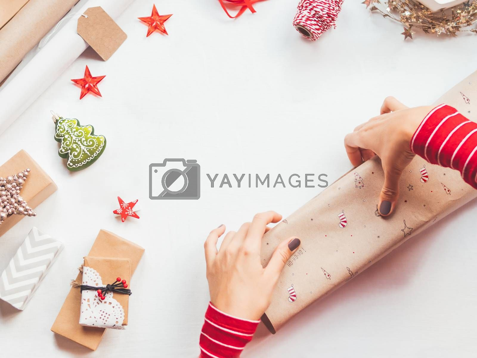 Top view on table with Christmas decorations. Woman draws New Year symbols on craft paper and wraps presents. Flat lay with copy space.