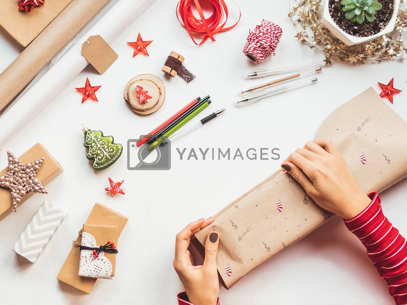 Top view on table with Christmas decorations. Woman draws New Year symbols on craft paper and wraps presents. Flat lay.