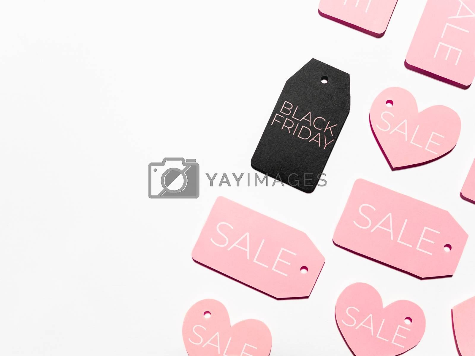 Top view on pattern of many pink and one black clothes tags on white background. Glamorous labels. Black Friday sale and shopping. Flat lay.