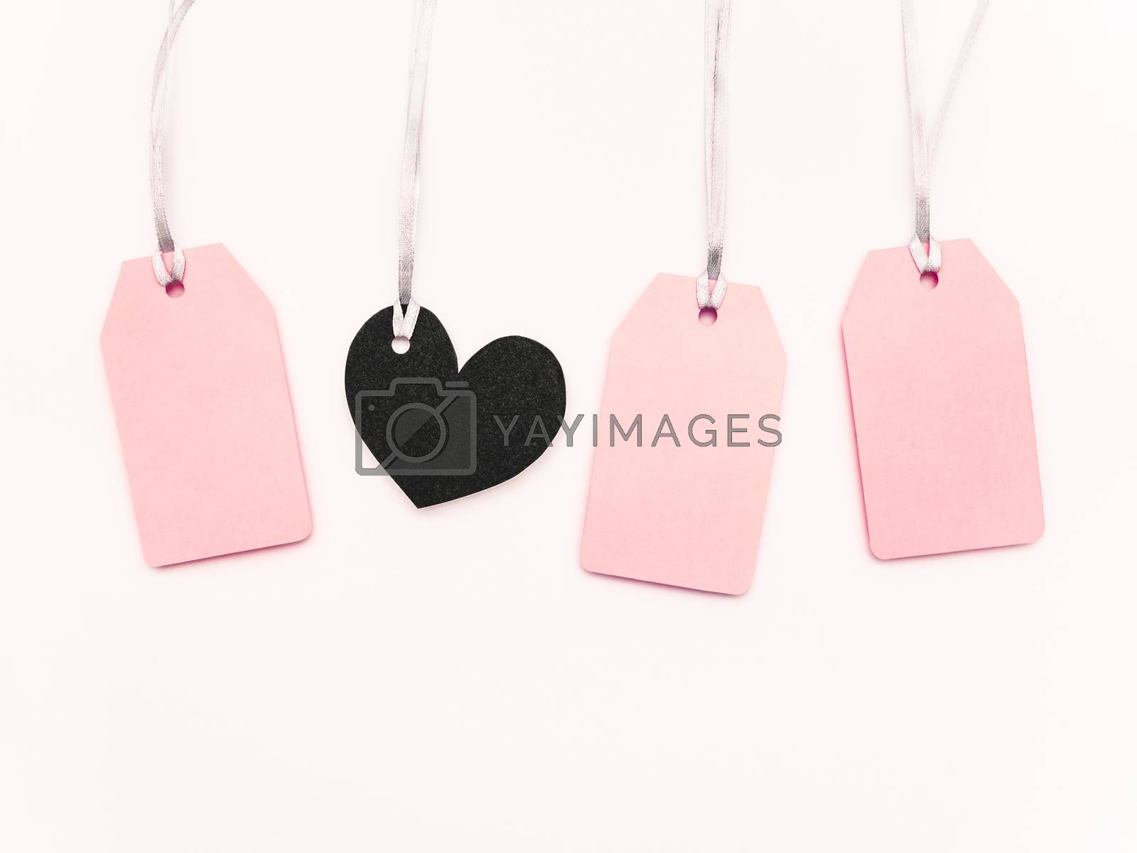 Pink and black heart clear tags on white background. Glamorous labels on silver threads with copy space. Symbol of Black Friday sale and shopping. Top view, flat lay.