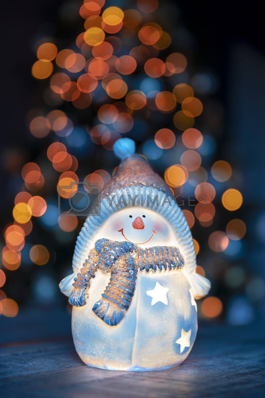 Little decorative snowman toy on the table over glowing Christmas tree background, happy winter holidays, traditional New Year and winter character