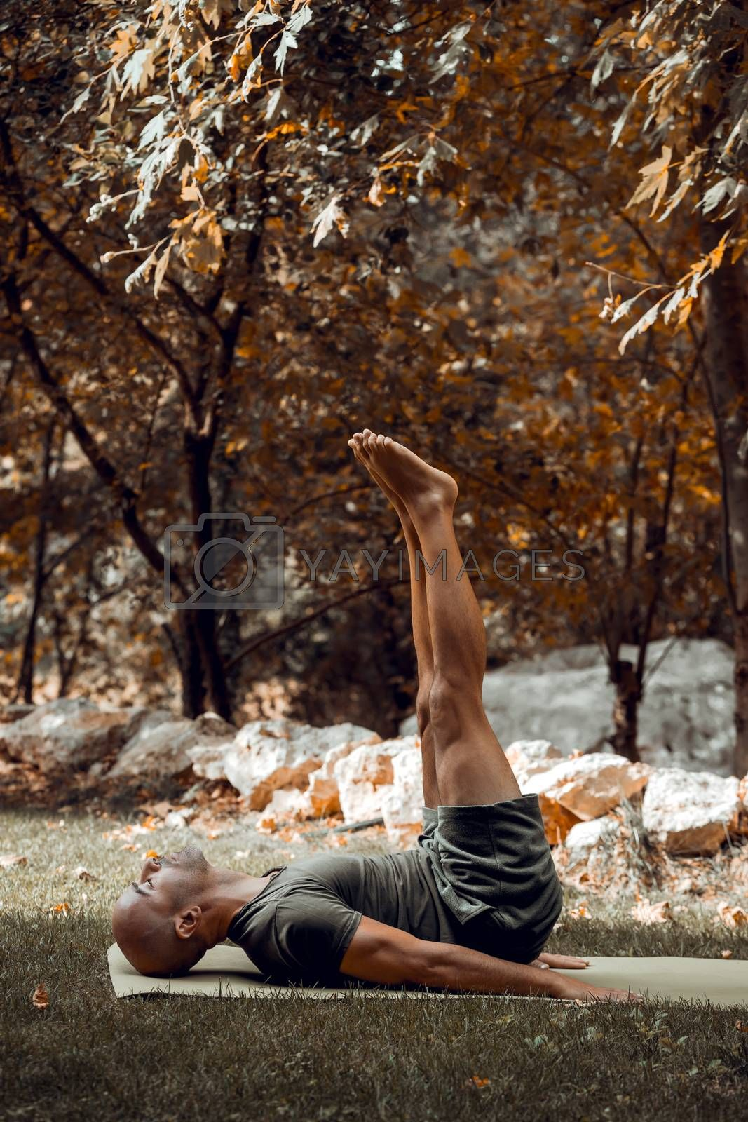 Handsome Sportive Man Doing Yoga in Autumnal Park. Athletic Guy Training Outdoors. Enjoying Peaceful Workout. Healthy Lifestyle.